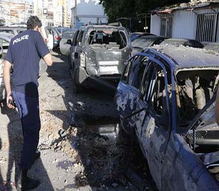A policeman inspects damaged cars after two rockets hit houses and parked cars in Beirut suburbs