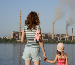 """concept """"care for future"""". Mother and daughter look at factory polluting an air"""