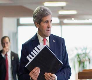 U.S. Secretary of State John Kerry picks up his notebook after answering questions from members of the media before his departure from Ben Gurion International Airport in Tel Aviv, December 6, 2013. REUTERS/Pablo Martinez Monsivais/Pool (ISRAEL - Tags: POLITICS)