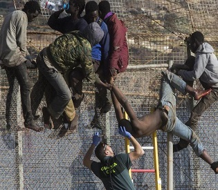 hromedia African migrants perched on fence In Spanish enclave of Melilla eu news2