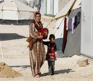 A Syrian refugee woman walks with her children at the Zaatri refugee camp