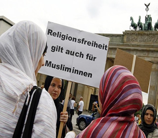 "A woman holds a placard reading ""Religious freedom applies to Mu"