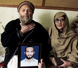Muhammad Azeem and Sajida Parveen, the parents of Ehsan Azeem, who was sentenced to death by a military court, react while holding their son's picture during an interview with Reuters in Rawalpindi