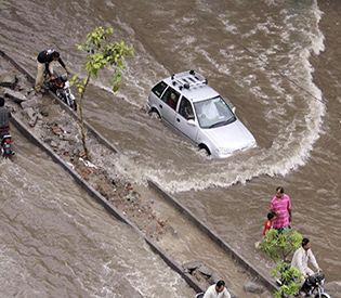 A car drives through a flooded road caused by heavy rains in Lahore, Pakistan, Tuesday, July 21, 2015. A Pakistani local government spokesman says this week's flash floods triggered by monsoon rains in the country's north have killed at least two people and damaged several homes, roads and bridges. (AP Photo/K.M. Chaudary)