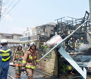 The tail section of a crashed light plane (C) and burning house are seen after the plane went down in a residential area and burst into flames, in Chofu, outskirt of Tokyo, in this photo taken by Kyodo July 26, 2015. A small airplane crashed into a residential area of the Japanese capital, Tokyo, on Sunday, setting fire to houses and cars and injuring at least two people, the Tokyo Fire Department said. Mandatory credit REUTERS/Kyodo  ATTENTION EDITORS - FOR EDITORIAL USE ONLY. NOT FOR SALE FOR MARKETING OR ADVERTISING CAMPAIGNS. THIS IMAGE HAS BEEN SUPPLIED BY A THIRD PARTY. IT IS DISTRIBUTED, EXACTLY AS RECEIVED BY REUTERS, AS A SERVICE TO CLIENTS. MANDATORY CREDIT. JAPAN OUT. NO COMMERCIAL OR EDITORIAL SALES IN JAPAN.      TPX IMAGES OF THE DAY