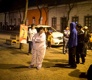 Residents stand on a street outside their houses after an earthquake hit Chile's central zone,  in Santiago