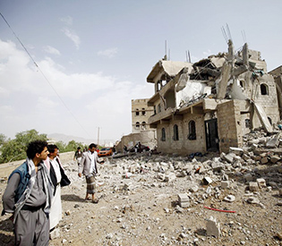People look at the rubble of a house destroyed by a Saudi-led airstrike in Yemen's capital Sanaa