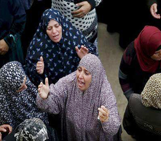 Relatives of Palestinian Yehia Taha, who medics said was killed by Israeli troops during clashes, mourn during his funeral in the West Bank village of Qatnna