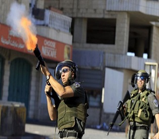 police officer fires a tear gas canister at Palestinian protesters during clashes in the West Bank city of Bethlehem