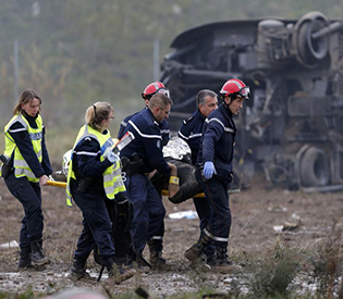 Rescue workers carry a victim on a stretcher from the wreckage of a test TGV train that derailed and crashed in a canal outside Echwersheim near Strasbourg