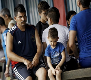 A Cuban migrant man and his son await to receive a humanitarian visa at a border post with Panama in Paso Canoas, Costa Rica