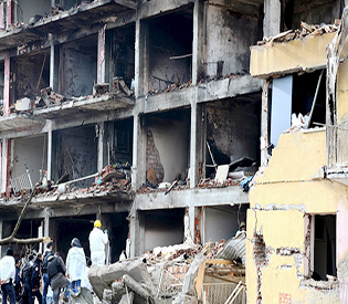 Police forensic experts examine a destroyed police station in Cinar in the southeastern city of Diyarbakir