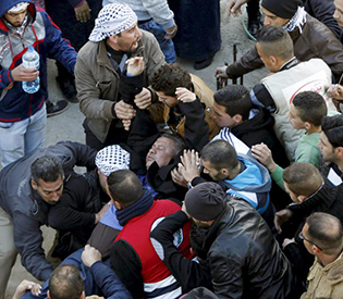 Mourners carry a fainted man during the funeral Palestinian Ali Taqatqa and Ali Thawabteh in the West Bank village of Beit Fajjar
