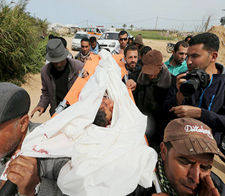 Mourners carry the body of 10-year-old Palestinian boy Yassin Abu Khoussa, whom medical officials said was killed by fragments from a missile fired by an Israeli aircraft, during his funeral in the northern Gaza Strip