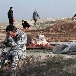 Iraqi police officer reacts after finding innocent young bodies in mass grave